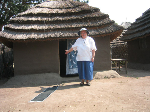 Deb in front of her tukel, a grass roof hut